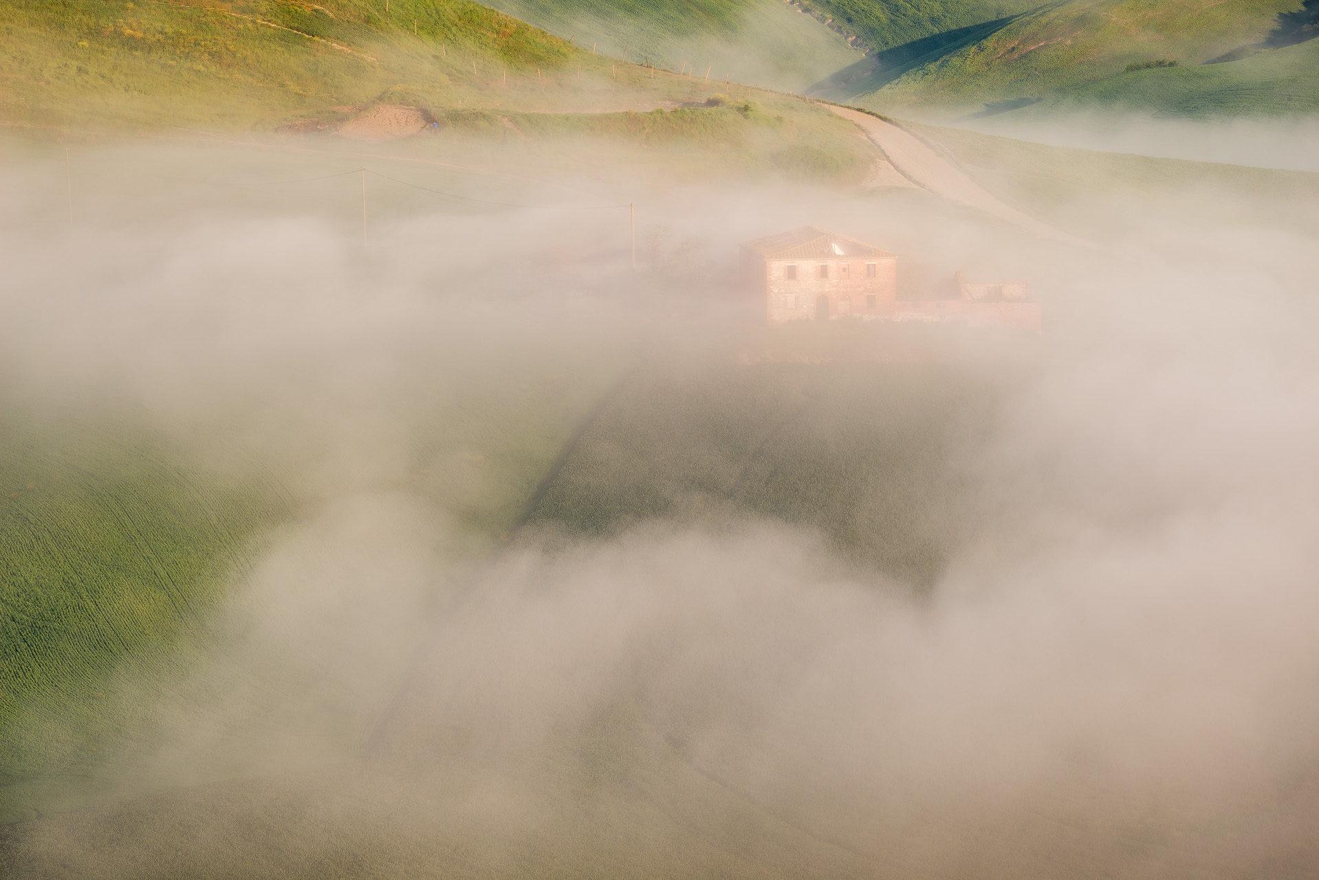Casali nella nebbia nei pressi di Asciano, cuore delle Crete Senesi. Toscana (Siena)